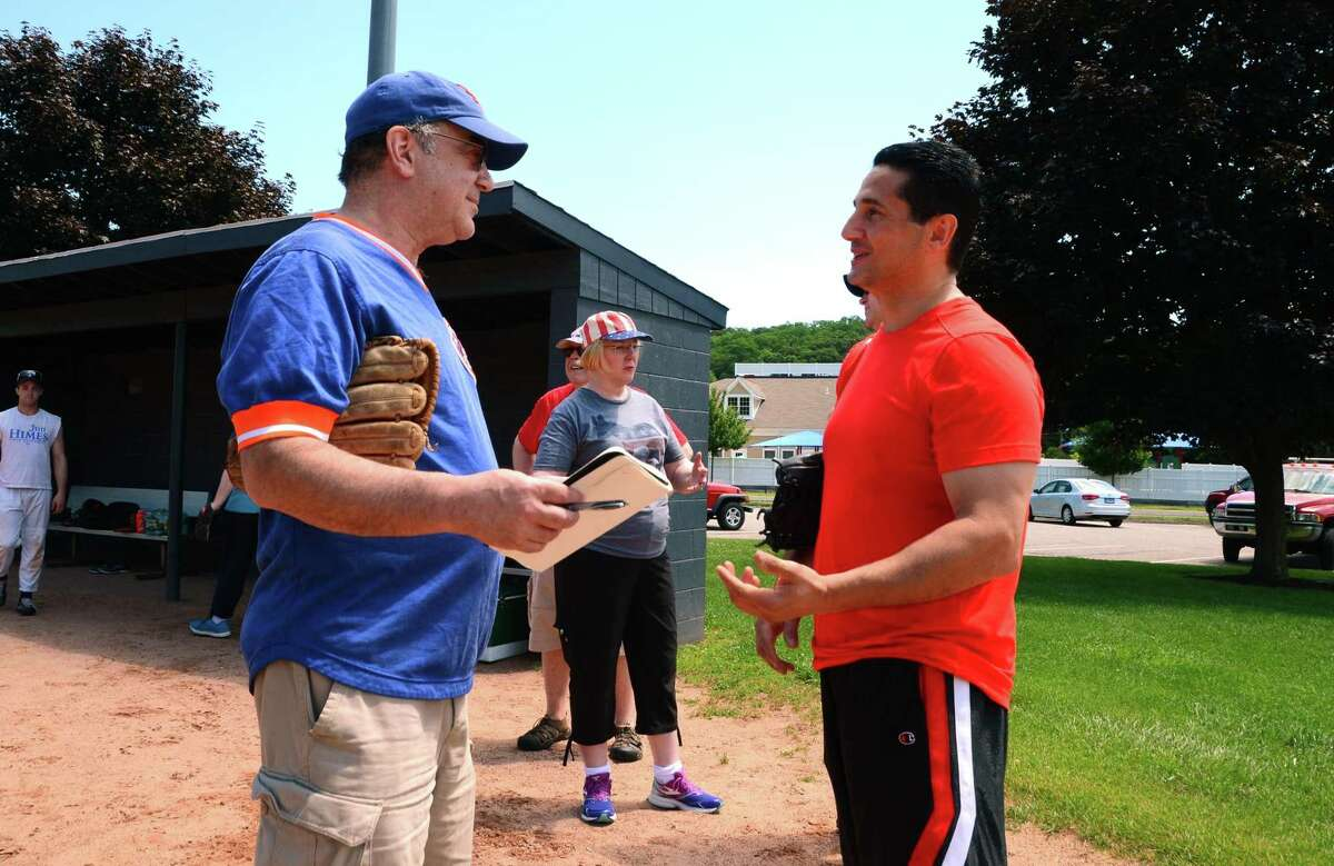 """Manager Eric Fenwick, left, with the Wilton Democrats, chats with Republican team manager Joseph Favarolo before the start of the 51st annual Frivolity Bowl held at Wilton High School in Wiltonl, Conn., on Saturday July 4, 2015. The tradition began in 1966, after the Democrats challenged the Republicans to a softball game on the coming Fourth of July and the Republicans responded, """"That's frivolous."""""""
