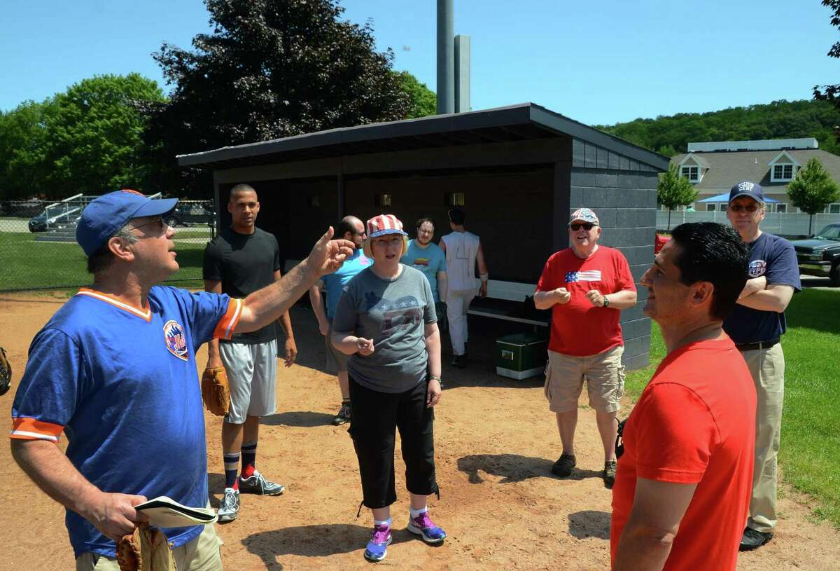 """Manager Eric Fenwick, left, with the Wilton Democrats, tosses up a quarter as Republican team manager Joseph Favarolo looks on to start the 51st annual Frivolity Bowl held at Wilton High School in Wiltonl, Conn., on Saturday July 4, 2015. The tradition began in 1966, after the Democrats challenged the Republicans to a softball game on the coming Fourth of July and the Republicans responded, """"That's frivolous."""""""