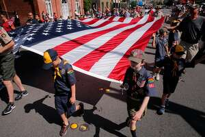Boy scout troops 991 and 146 carry a huge American flag during the annual Fourth of July parade through downtown Redwood City, Ca., on Tuesday July 4, 2017.