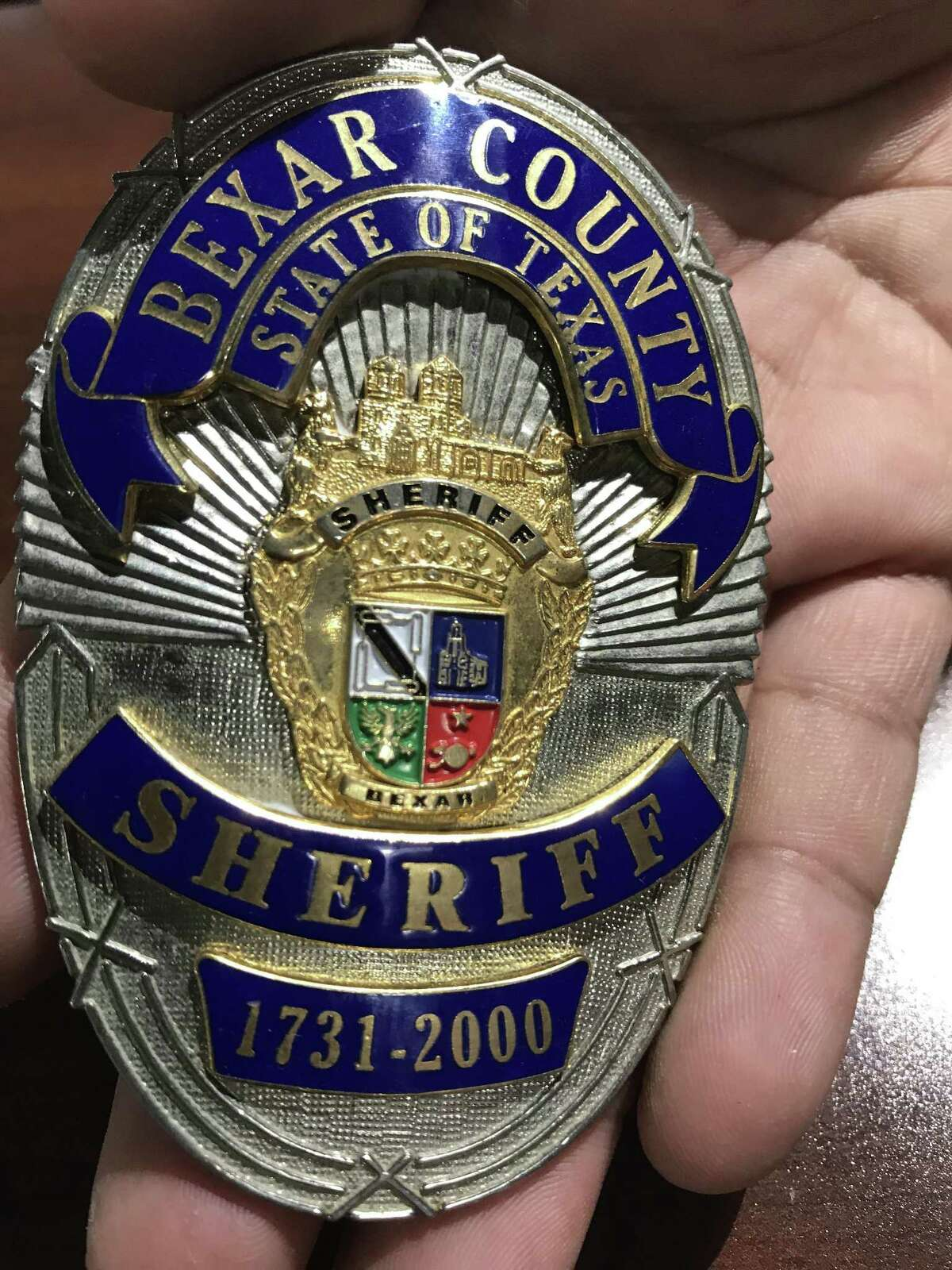 This is a commemorative Bexar County Sheriff's badge released to celebrate the turn of the millennium. The front shows the seal of Bexar County and the years 1731-2000. The back has an up-to-then complete list of sheriff deputies killed in the line of duty.