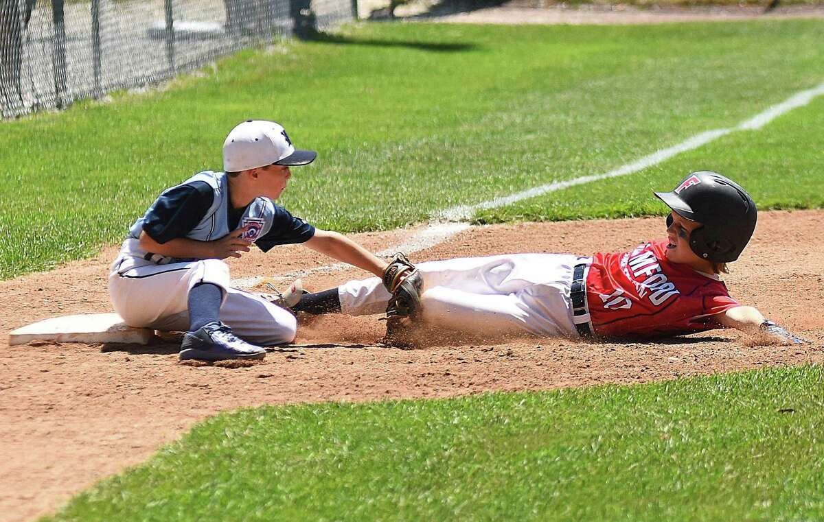 Wilton third baseman Luke Perna, left, tags out Stamford American's Patrick Leonard, who was trying to stretch a double into a triple during the first inning of Saturday's District 1 10-year-old Little League All-Star double-elimination playoff round at Bill Terry Field in Wilton.