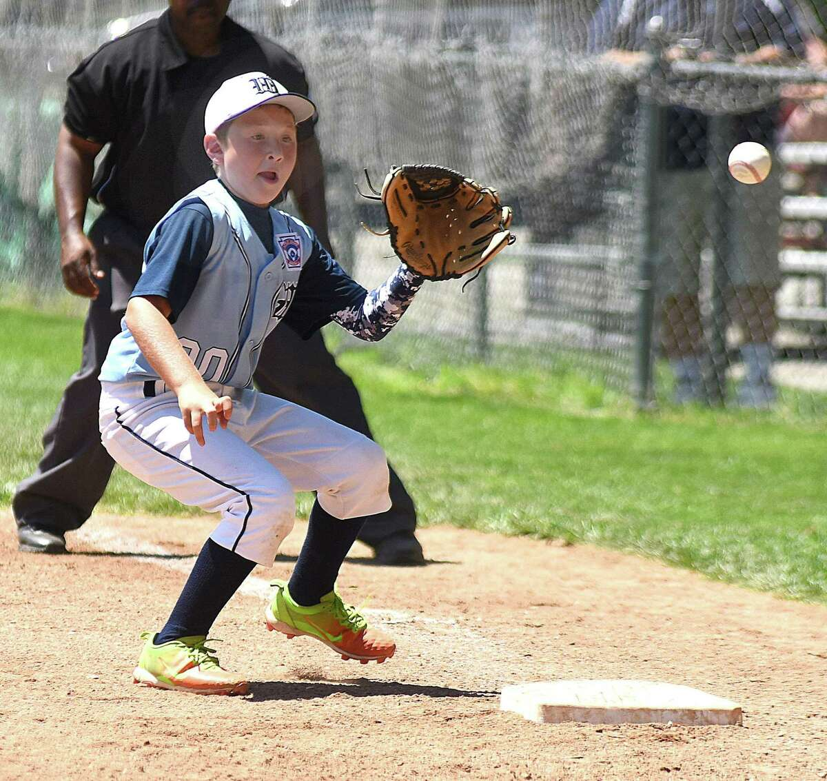 Wilton first baseman Stef Cross plays a bounding ball for an out during Saturday's District 1 10-year-old Little League All-Star double-elimination playoff round at Bill Terry Field in Wilton.