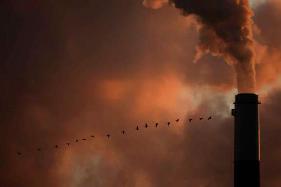 FILE - In this Saturday, Jan. 10, 2009, file photo, a flock of geese fly past a smokestack at the Jeffery Energy Center coal power plant near Emmitt, Kan. Hundreds of corporations, insurance companies and pension funds are calling on world leaders gathering for a U.N. summit on climate change this week to attack the problem by making it more costly for businesses to pollute. (AP Photo/Charlie Riedel, File)