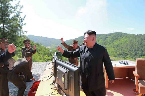 """Kim Jong Un reacts Tuesday to the test-firing of a missile, in a photo released by the official North Korean news agency. He said the launch was a Fourth of July """"gift"""" to the United States."""