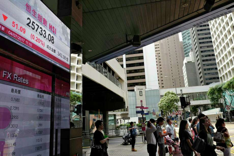 People stand next to an electronic board showing the Hong Kong Stock Exchange index, Tuesday, July 4, 2017, in Hong Kong, China. Australian shares jumped Tuesday as investors awaited an interest rate decision by the central bank, while other Asian shares were mixed Tuesday ahead of a U.S. trading holiday. (AP Photo/Vincent Yu) ORG XMIT: XVY105 Photo: Vincent Yu / Copyright 2017 The Associated Press. All rights reserved.