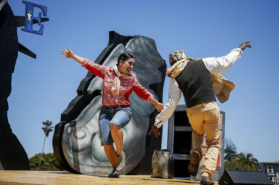 "Marilet Martinez, left, playing an undocumented woman from Mexico, and Rotimi Agbabiaka, right, playing an immigrant from Somalia, dance with the Tony-winning San Francisco Mime Troupe during the opening day performance of ""Walls"" written by Michael Gene Sullivan and directed by Edris Cooper-Anifowoshe in Mission Delores Park in San Francisco on Tuesday, July 4, 2017. Photo: Nicole Boliaux, The Chronicle"