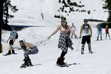 Snow boarders and skiers didn't bundle up as temperatures hovered in the high 60's to low 70's at the Squaw Valley Ski Resort, Saturday, July 1, 2017, in Squaw Valley, Calif. Because of this years heavy snow fall Squaw Valley is expected to be open through the 4th of July, only the fourth time the resort has been open for skiing in July. (AP Photo/Rich Pedroncelli)