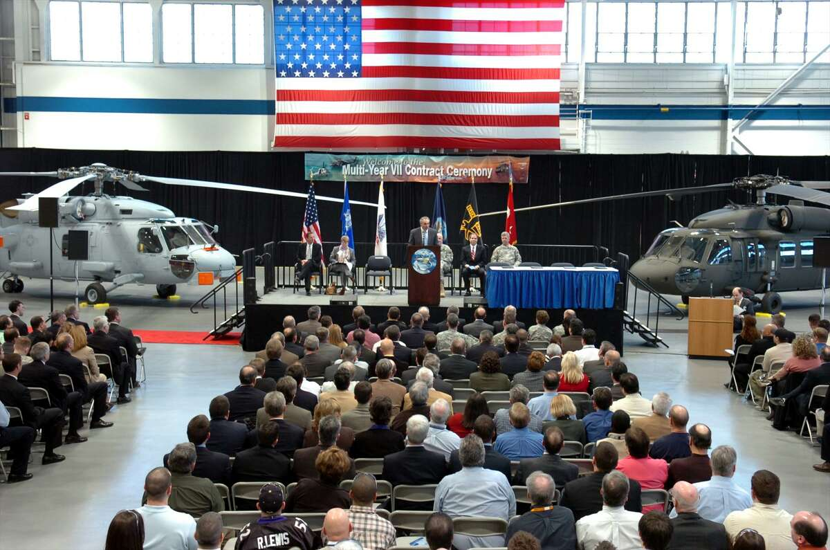 Former Sikorsky Aircraft President Jeffrey P. Pino speaks during a 2008 ceremony marking the signing of multi-year VII contracts for H-60 Black Hawk (seen here right) and Seahawk (seen here left) helicopters for the U.S. Army and U.S. Navy.