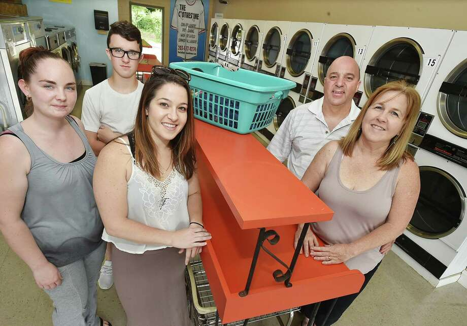 Jeff and Ellen Dorosh, of Naugatuck, owners of The Clothesline Laundromat and Dry Cleaners at 249 Naugatuck Avenue in Milford, Conn. with two of their four children, Elyse, 27, center, David, 16, and their employee Samantha Checca, at left. The Clothesline offers coin-op laundry, dry cleaning wash, dry and fold and commercial laundry seven days a week. Photo: Catherine Avalone / Hearst Connecticut Media / Connecticut Post