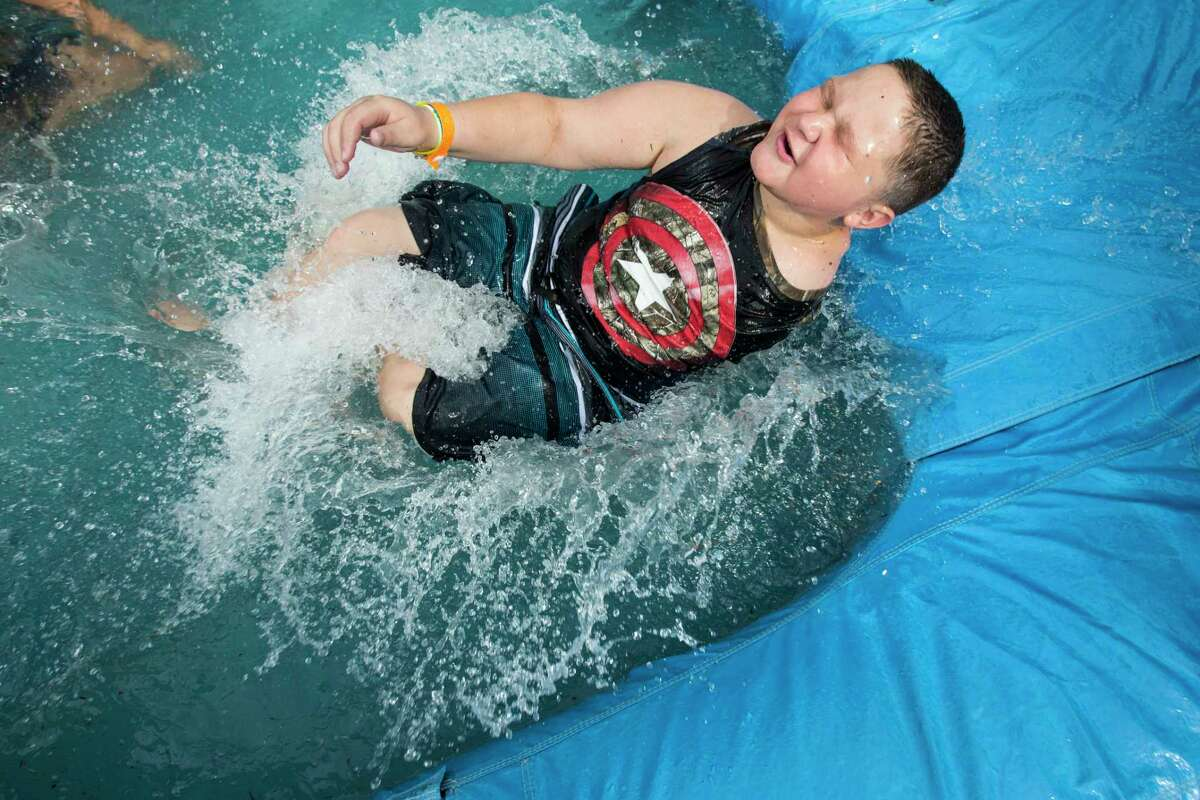 Damon Billeck splashes down at the bottom of a water slide at MD Anderson's Camp Star Trails. Damon has been battling osteosarcoma for the past couple years, and this is his second summer at camp.