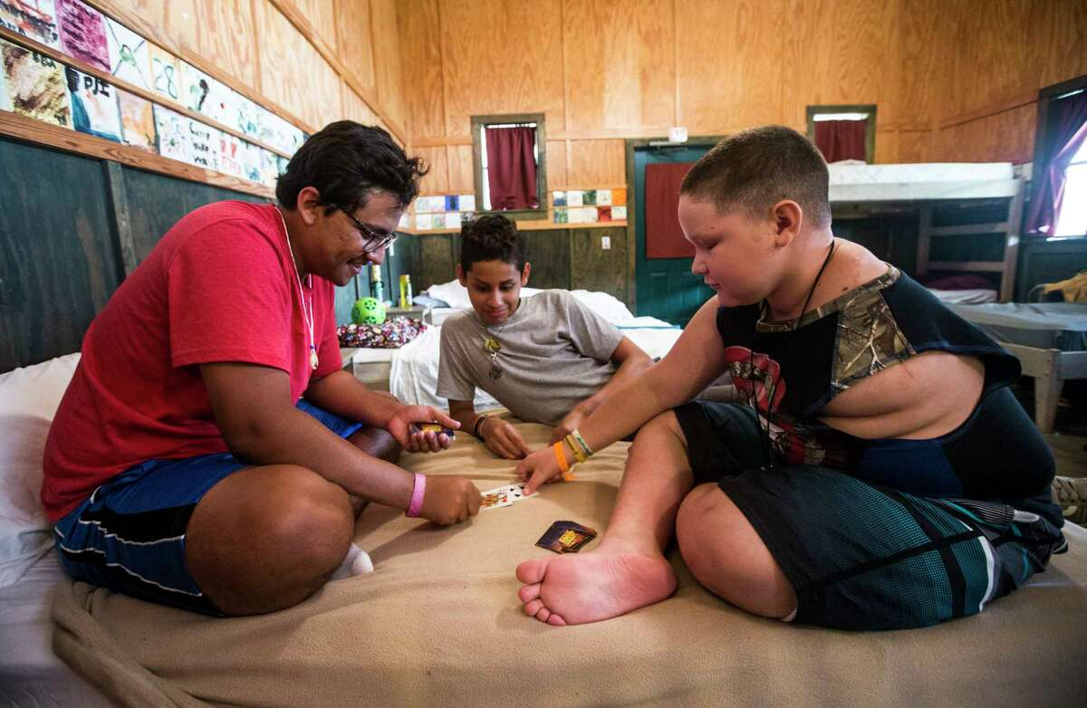 Camp counselor Tito Castaneda plays cards with campers Kevin Lopez and Damon Billeck in their cabin at MD Anderson Children's Cancer Hospital's Camp Star Trails.