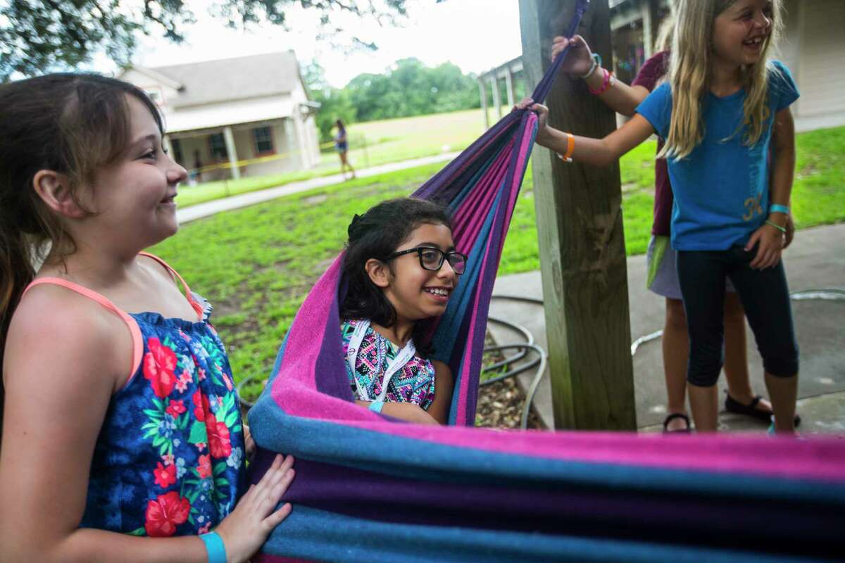 Joalie Lerado, 9, swings a in a hammock outside her cabin at MD Anderson Children's Cancer Hospital's Camp Star Trails.