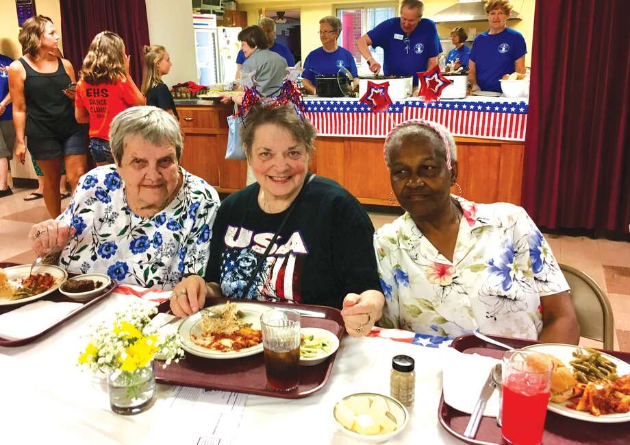 Eating lunch recently at Immanuel United Methodist Church are, from left, Kathy Erspamer, Linda Dillon and Mary Nunn. Faith in Action volunteers are serving meals behind them. Photo: Steve Horrell