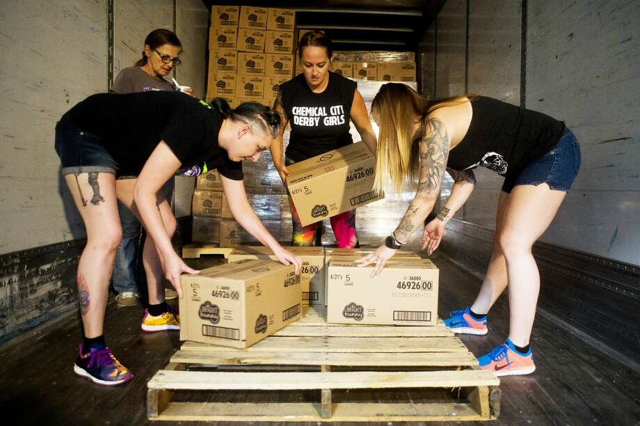 From left to right, Jamie Griffin of Bay City, Wendy Adams of Bay City and Hilary Peil of Bay City, all members of the Chemical City Derby Girls roller derby team, work to unload a delivery of over 555,000 diapers to The Diaper Alliance on Wednesday, July 5, 2017 in Midland. Photo: (Katy Kildee/kkildee@mdn.net)