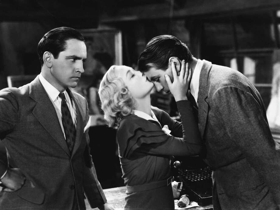Gilda Farrell (Miriam Hopkins) kisses painter George Curtis (Gary Cooper) on the forehead as playwright Tom Chambers (Fredric March) looks angrily on in the 1933 comedy film Design for Living. Photo: John Springer Collection / Corbis Via Getty Images / This content is subject to copyright.