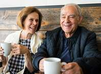 Senior couple, a caucasian woman and a hispanic man,  smiling having a cup of coffee in a coffee shop
