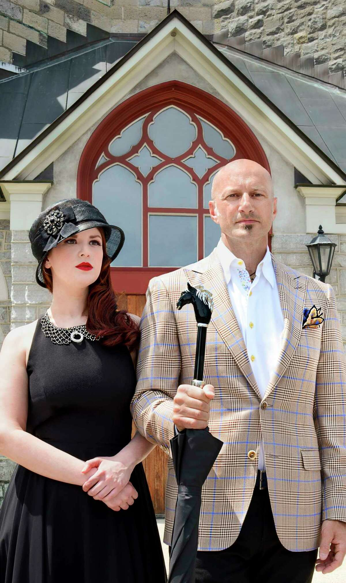"""Models pose for an """"American Gothic"""" inspired fashion shoot in Saratoga Springs, N.Y. on Thursday, June 8, 2017. Erin Hedderman wears a Aidan Mattox high-neck black chiffon handkerchief dress with exposed zipper and cut-out back from Fancy Schmancy, accented by a sterling silver and diamond circle necklace available exclusively at Frank Adams Jewelers. Her black cloche hat with bow detail and pewter broach created by Susanne Dura, also available at Fancy Schmancy. Robert Amore wears clothing from his store, Amore Clothing. (Photo by Colleen Ingerto / Times Union)"""