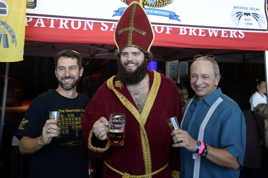 David Frazier, left, and Wayne Ingwerson pose with Jared Trimm, dressed as Saint Arnold at the brewery's booth during the Beaumont Craft Beer Festival at The Event Centre on Saturday afternoon.  Photo taken Saturday 9/24/16 Ryan Pelham/The Enterprise Photo: Ryan Pelham/The Enterprise