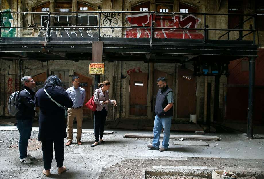 Sarah Madland (center), director of Policy and Public Affairs for the Recreation and Parks Department, tours the historic Geneva Car Barn and Powerhouse with staffers in San Francisco, Calif. on Wednesday, July 5, 2017. The city's Recreation and Parks Department will convert the former Muni repair facility, shuttered after the 1989 Loma Prieta earthquake, into a vibrant community performance and arts center. Photo: Paul Chinn, The Chronicle