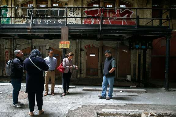 Sarah Madland (center), director of Policy and Public Affairs for the Recreation and Parks Department, tours the historic Geneva Car Barn and Powerhouse with staffers in San Francisco, Calif. on Wednesday, July 5, 2017. The city's Recreation and Parks Department will convert the former Muni repair facility, shuttered after the 1989 Loma Prieta earthquake, into a vibrant community performance and arts center.