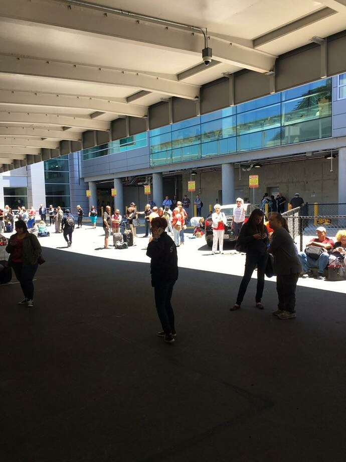 Passengers wait outside Terminal 1 after the baggage claim area was evacuated Wednesday afternoon. Photo: Courtesy Of Renai Bodley / Renai Bodley