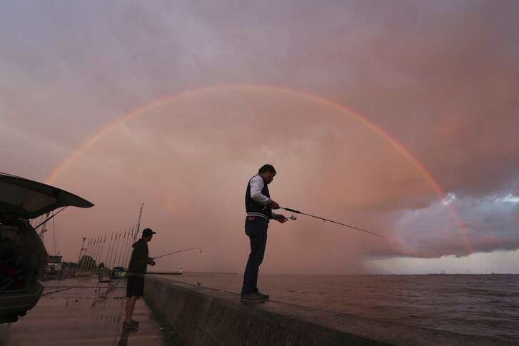 Two men fish under a rainbow in Portsmouth Harbour in Kingston, Ontario, June 3, 2017.