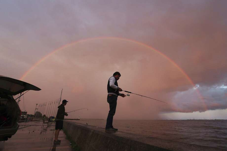 Two men fish under a rainbow in Portsmouth Harbour in Kingston, Ontario, June 3, 2017. Photo: Lars Hagberg /Associated Press / The Canadian Press