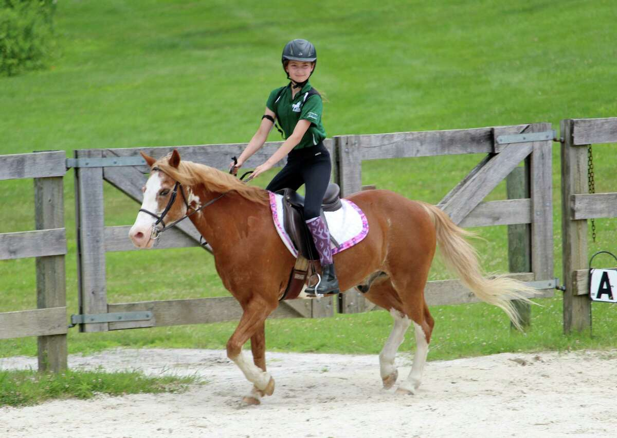 Susie Robinson rides her pony, Rebel, at Wilton Pony Club's summer camp on June 30, 2017.