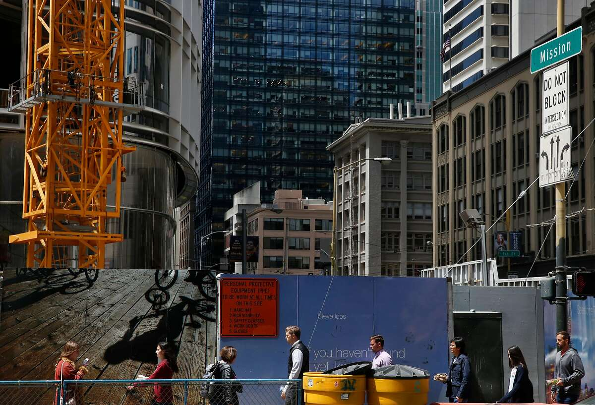 Pedestrians walk past the future spot of a plaza at the base of the new Salesforce Tower on the corner of Mission and Fremont streets July 5, 2017 in San Francisco, Calif.