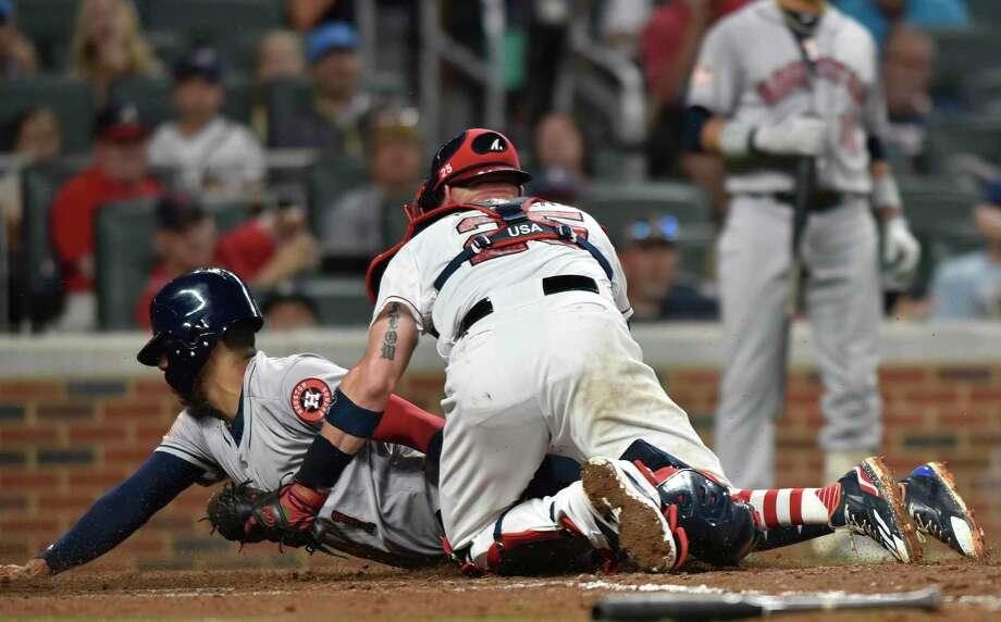 Atlanta Braves catcher Tyler Flowers fails to stop Houston Astros' Carlos Correa from sliding into home for a run during the third inning of a baseball game agains the Braves, Tuesday, July 4, 2017, in Atlanta. (AP Photo/Richard Hamm) Photo: Richard Hamm, Associated Press / AP