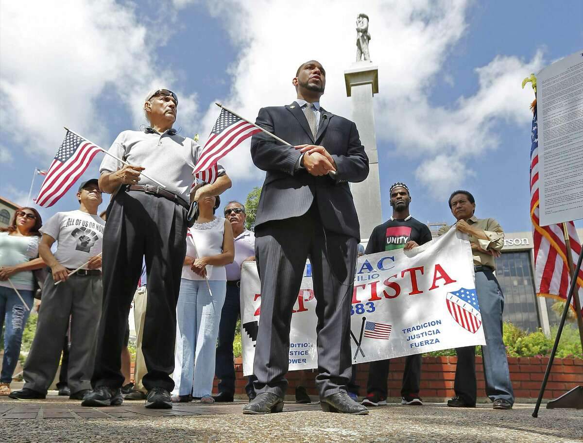 """Bexar County 4th Precinct Commissioner Tommy Calvert (center), Mario Salas of San Antonio Coalition of Human and Civil Rights (left) and others gather for a press conference to demand the Confederate monument at Travis Park be removed in light of recent efforts by Bexar County officials to take down confederate symbols on public property. Since the park is on city property, the city council would have to vote and approve such a decision. Calvert and Salas hope to persuade their city officials to take such action. The monument has been at the park since 1899 which has a statue of a confederate soldier facing South and the words, """"Our Confederate Dead"""" and """"Lest we forget"""" engraved on the monument. (Kin Man Hui/San Antonio Express-News)"""