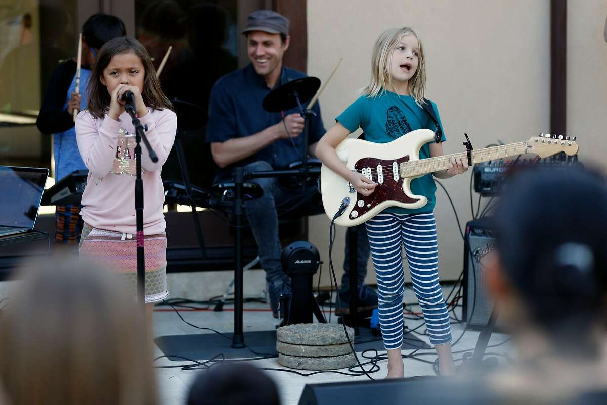 Raah Canada sings, Stella Goss plays the guitar and Mike Hoffman drums as kid band Good Stuff plays in the backyard of Google executive Lydia Mazzie's home in Menlo Park, Calif., on Thursday, June 29, 2017.