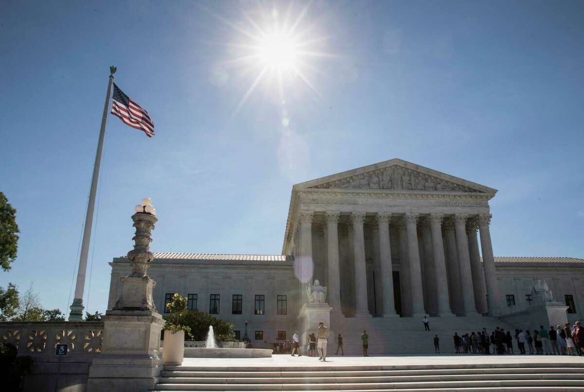 People visit the Supreme Court in Washington as justices issued their final rulings this term, including allowing the president's travel ban.