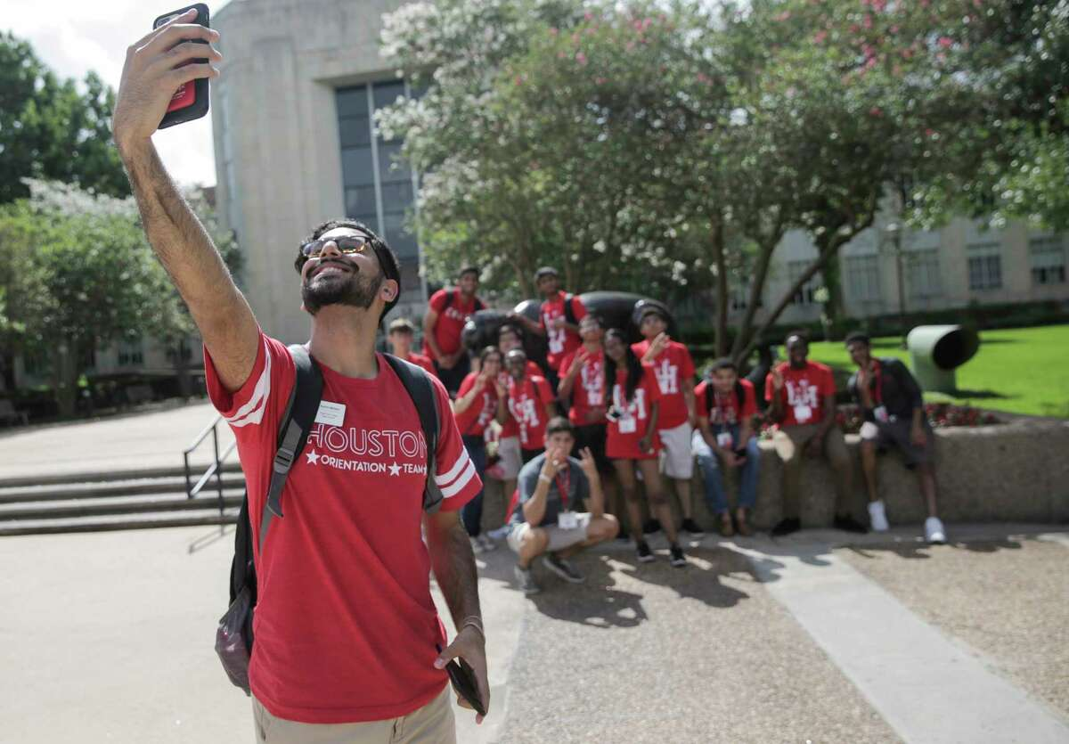 Karim Motani, a junior at UH, takes a group photo of incoming students during an orientation on campus.