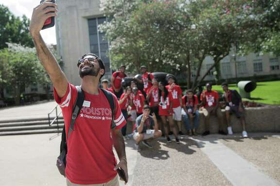 Karim Motani, a junior at UH, takes a group photo of incoming students during an orientation on campus. The university's decline in international applications follows three years of growth.