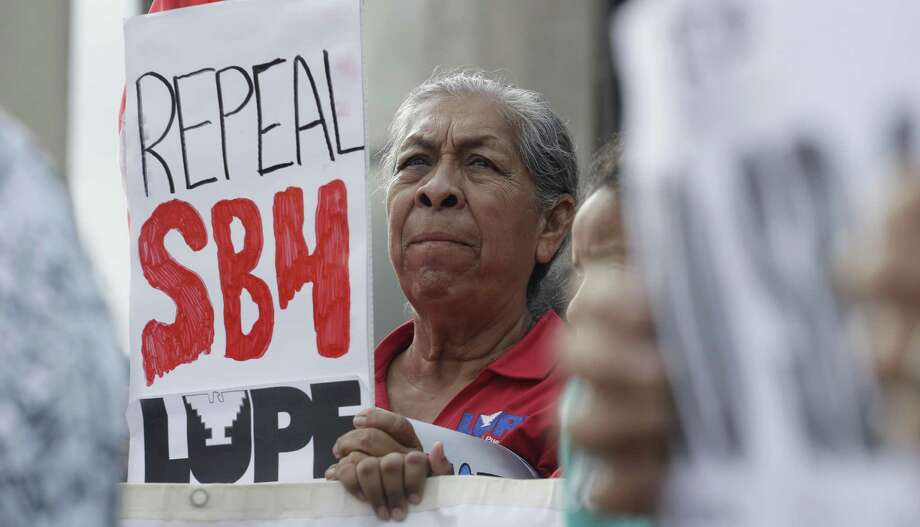 """Protesters gather outside the Federal Courthouse to oppose a new Texas """"sanctuary cities"""" bill that aligns with the president's tougher stance on illegal immigration, Monday, June 26, 2017, in San Antonio. A federal judge on Monday heard arguments before he decides whether a new Texas """"sanctuary cities"""" can take effect. (AP Photo/Eric Gay) Photo: Eric Gay, STF / Associated Press / Copyright 2017 The Associated Press. All rights reserved."""