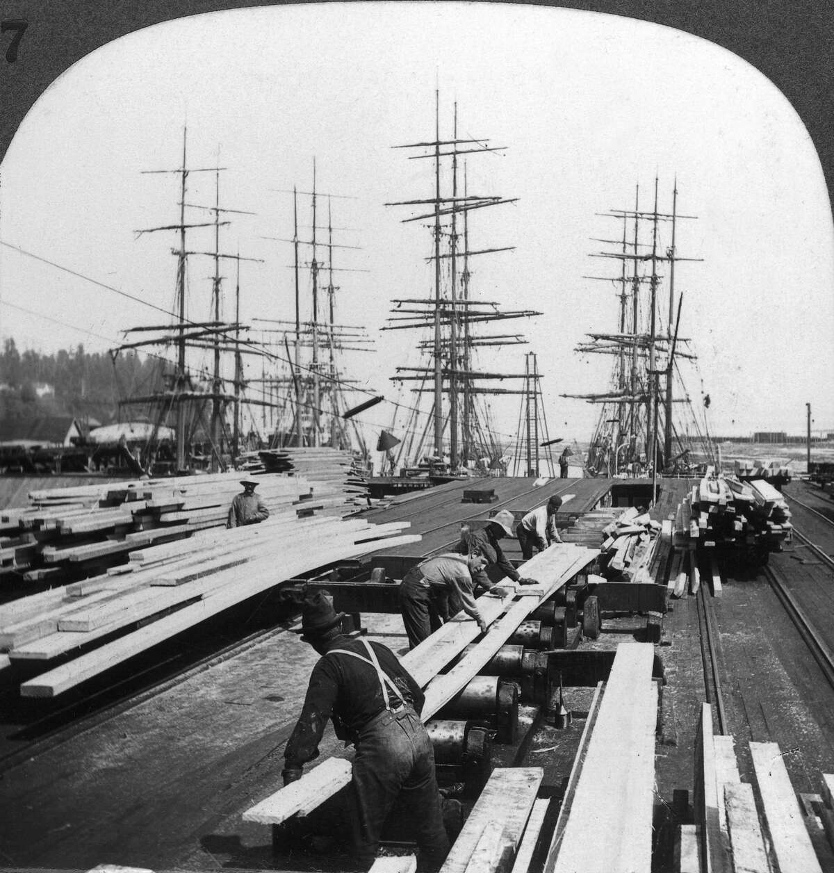 UNITED STATES - JANUARY 01: Loading of wooden planks in Blakely harbour near Seattle, Washington (U.S.), on three-masted boats, around 1900-1930. The quay is equipped with electrical lighting, as the picture shows. The wood, which came from Washington and Oregon's forests, was sent everywhere in the world: South Africa, South America, Japan, etc. (Photo by Keystone-France/Gamma-Keystone via Getty Images)