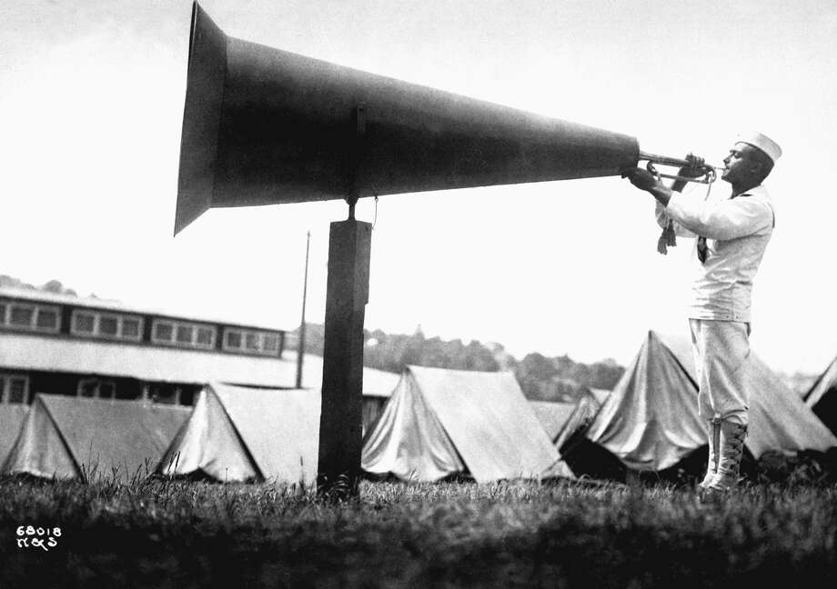 To wake the camp residents, a soldier amplifies the sound of his bugle by blowing into a giant megaphone at the United States Naval Training camp in Seattle, WA, 1917. (Photo by Webster & Stevens/Inteirm Archives/Getty Images) Photo: Interim Archives/Getty Images