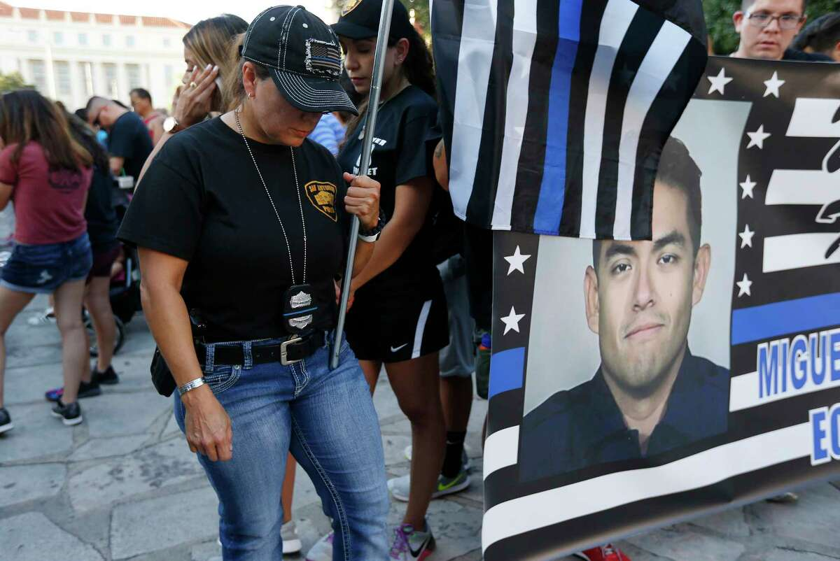 San Antonio Police Officer Leigh Holderby bows her head in prayer as hundreds gather at Alamo Plaza for the Walk of Honor to pay respect to fallen SAPD Officer Miguel Moreno on Wednesday, July 5, 2017. Moreno was shot and killed last Thursday while on patrol near the Tobin Hills area by San Antonio College. The walk started at the Alamo and concluded at Public Safety Headquarters.
