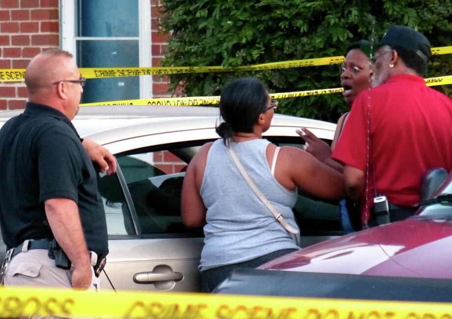 A woman who demanded to be let into the scene speaks with officers at Trumbull Gardens in Bridgeport on Wednesday as police investigate the deaths of two people in an apartment at the complex. Photo: Christian Abraham / Hearst Connecticut Media / Connecticut Post