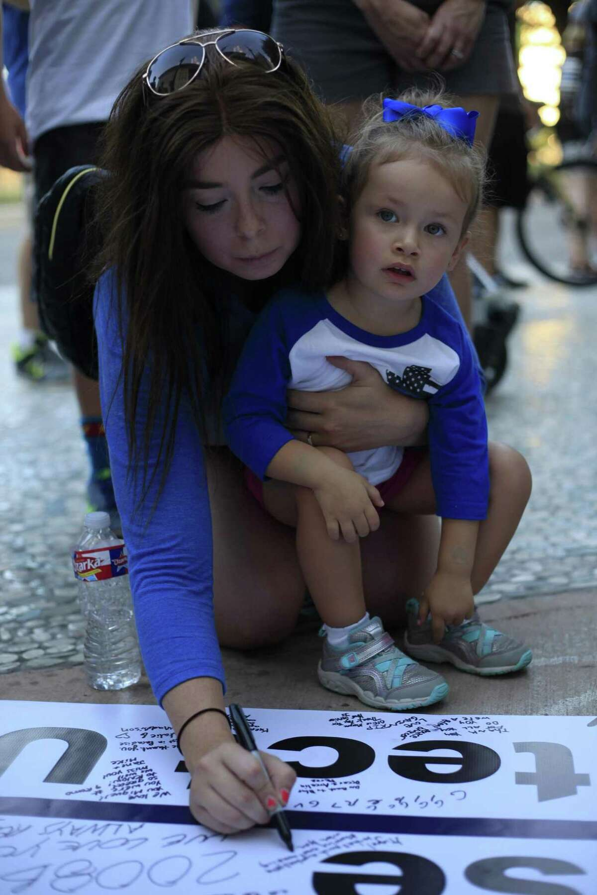 Alexandria Rosales and daughter Olivia sign the banner for fallen officer Miguel Moreno at the Public Safety Headquarters on July 5, 2017.