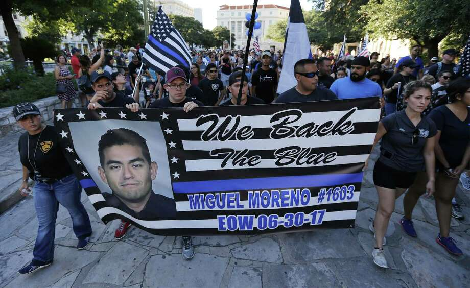 A banner honoring fallen officer Miguel Moreno is shown as hundreds gather at Alamo Plaza for the Walk of Honor to pay respect to Moreno on Wednesday, July 5, 2017. Moreno was shot and killed last Thursday while on patrol near the Tobin Hills area by San Antonio College. The walk started at the Alamo and concluded at Public Safety Headquarters. (Kin Man Hui/San Antonio Express-News) Photo: Kin Man Hui, Staff / San Antonio Express-News / ©2017 San Antonio Express-News