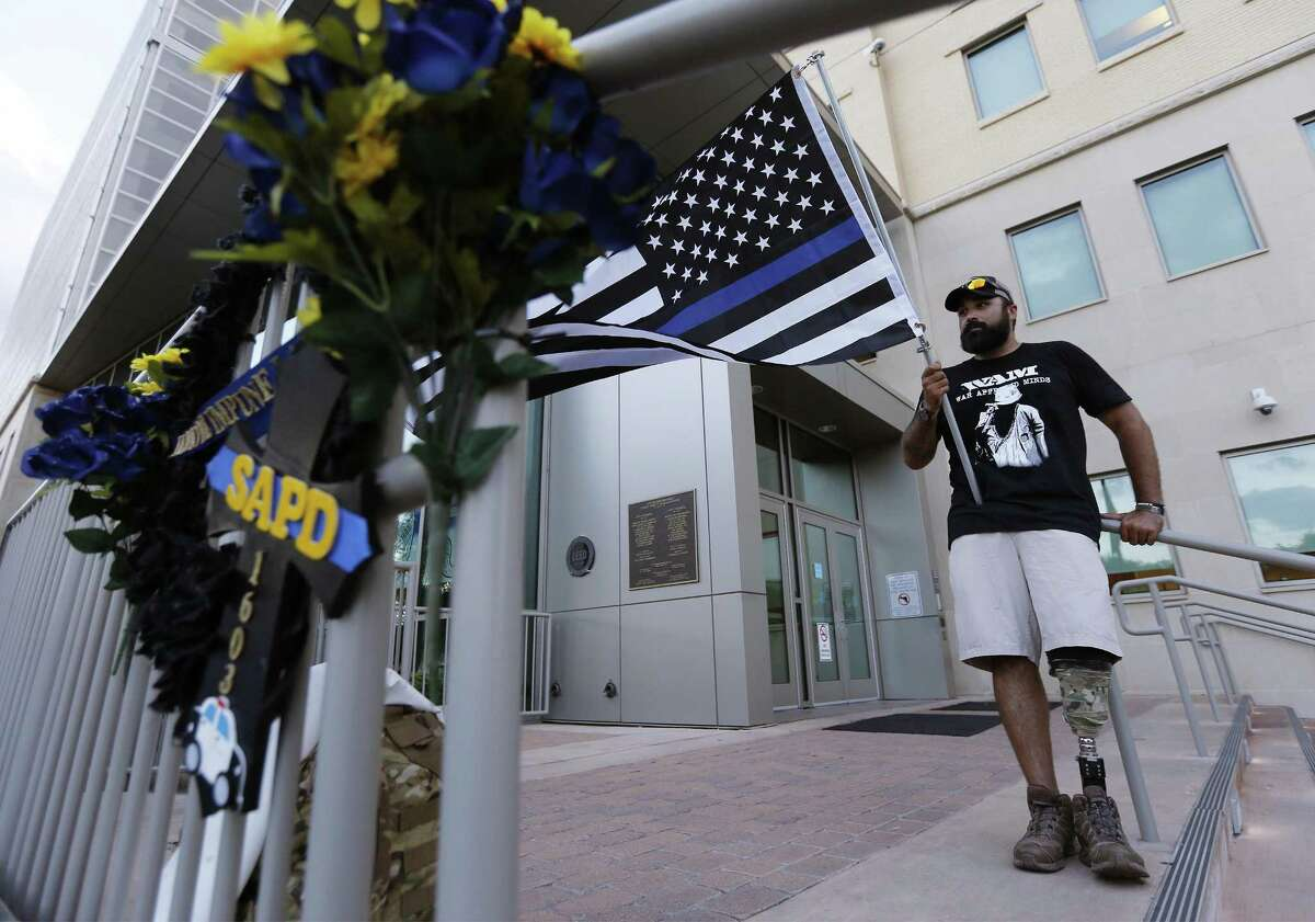 Army veteran Derrick Ross holds a flag to honor fallen police officers near a wreath at Public Safety Headquarters after hundreds marched from Alamo Plaza for the Walk of Honor to pay respects to fallen SAPD Officer Miguel Moreno on Wednesday, July 5, 2017. Moreno was shot and killed last Thursday while on patrol near the Tobin Hills area by San Antonio College. The walk started at the Alamo and concluded at Public Safety Headquarters. The wounded warrior said he always makes an effort to thank police officers for putting their lives on the line. (Kin Man Hui/San Antonio Express-News)