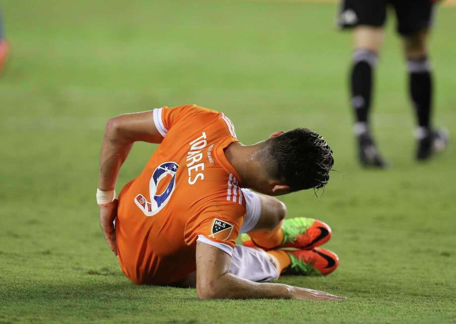 Dynamo forward Erick Torres (9) touches his lower back after having a contact with Montreal Impact goalkeeper Evan Bush (1). Torres was fined by MLS for simulation on the play. Photo: Yi-Chin Lee, Houston Chronicle / © 2017  Houston Chronicle