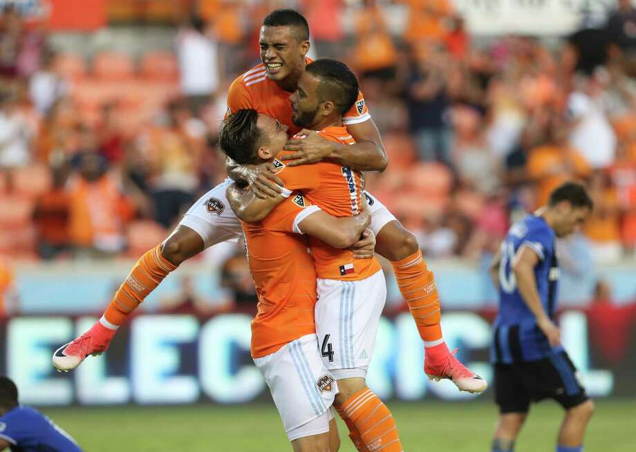 Mauro Manotas, top,  and Erick Torres, left, help Alex celebrate his first-half goal. Photo: Yi-Chin Lee, Staff / © 2017  Houston Chronicle