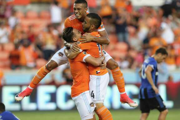 Mauro Manotas, top,  and Erick Torres, left, help Alex celebrate his first-half goal.
