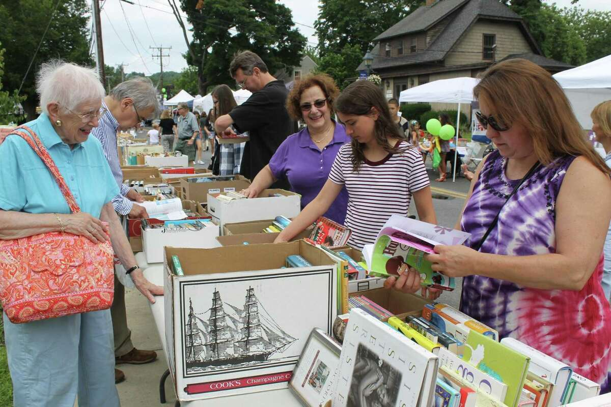 Wilton residents and visitors sift through the library's book and CD collection at last year's annual Sidewalk Sales.