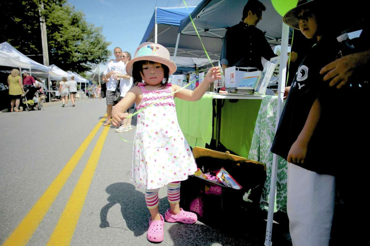 Kayla Tong, 3 1/2, holds a balloon at Wilton's 5th annual street fair and sidewalk sale on Old Ridgefield Road Saturday July 16, 2016.