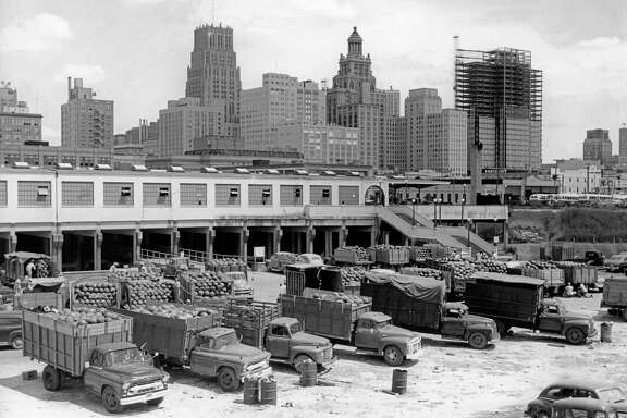 1955 - Old farmers market along Buffalo Bayou at the foot of Prairie Avenue. Bank of Southwest building at 909 Travis and Milam under construction at right.