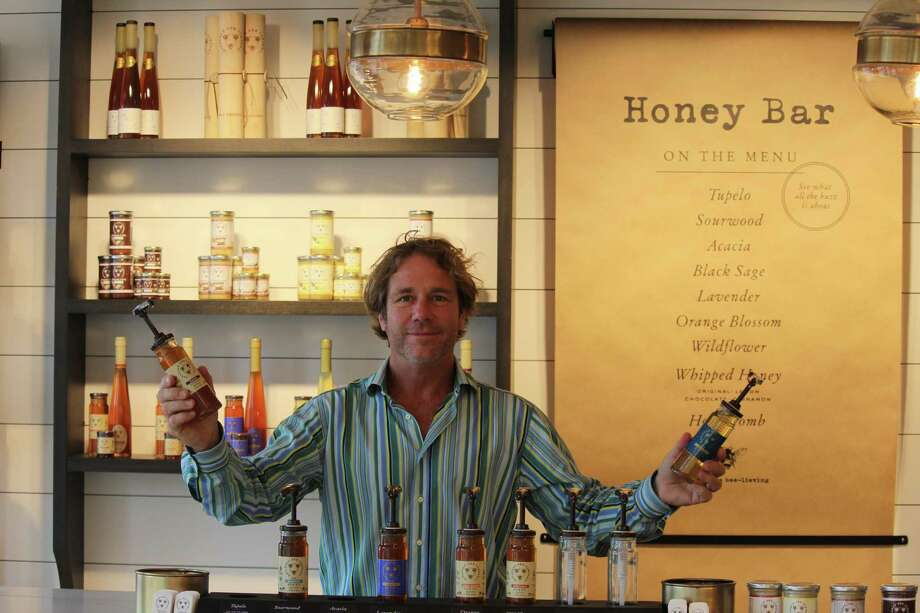 Ted Dennard, president and founder of Savannah Bee Company, poses at the honey bar of his store's new Bedford Square location on Church Lane. Photo: Chris Marquette / Hearst Connecticut Media / Westport News